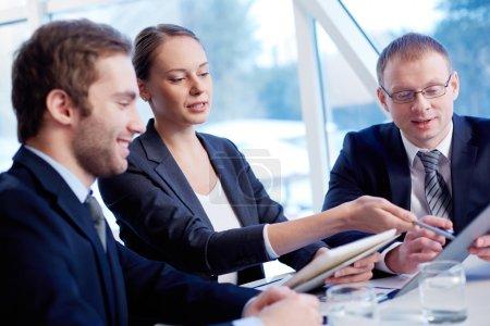 Photo pour Groupe de confiance associés discutant de papier à la réunion - image libre de droit