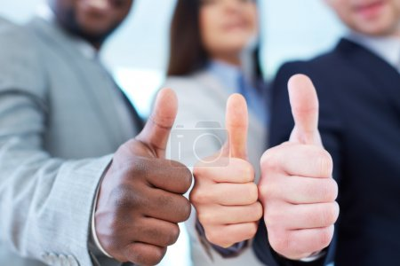 Photo for Three business partners keeping thumbs up - Royalty Free Image