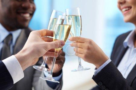 Photo pour Gros plan des mains de partenaires commerciaux acclamant vers le haut avec les flûtes de champagne doré - image libre de droit