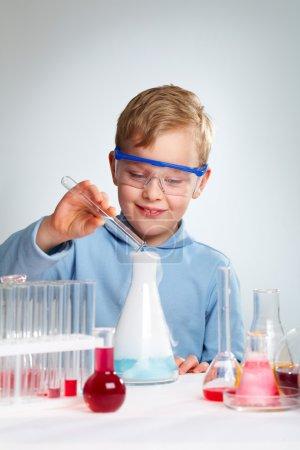 Photo pour Plan vertical d'un garçon enthousiaste de l'école heureux de réussir l'expérience - image libre de droit