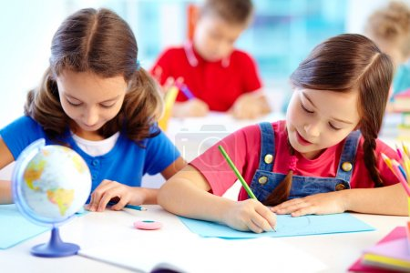 Photo for Portrait of lovely girls drawing at workplace with schoolboys on background - Royalty Free Image