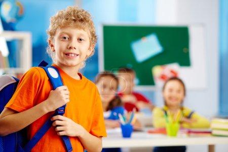 Photo pour Portrait d'écolier mignon avec sac à dos regardant la caméra avec ses camarades de classe sur fond - image libre de droit