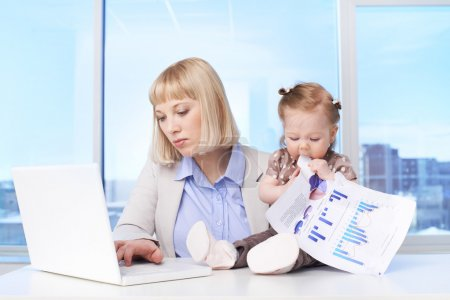 Confident businesswoman typing at workplace with her baby tasting document near by