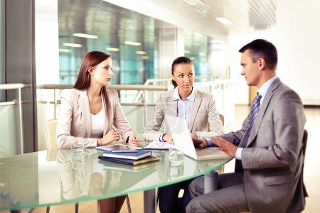 Photo pour Groupe de trois partenaires commerciaux qui interagissent lors d'une réunion au bureau - image libre de droit