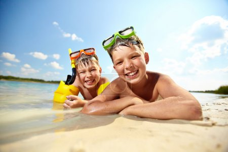Photo for Photo of happy siblings lying on sand on summer vacation - Royalty Free Image