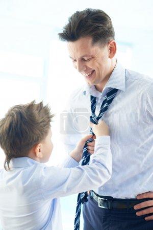 Photo pour Photo de garçon heureux aidant son père cravate cravate - image libre de droit