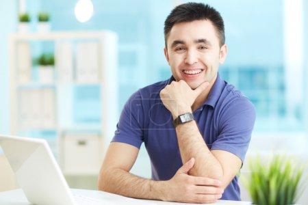 Photo pour Portrait d'homme d'affaires joyeux regardant la caméra dans le bureau - image libre de droit