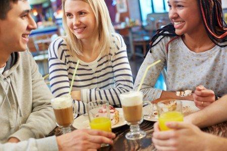 Foto de Imagen de amigos adolescentes chateando mientras comer el postre de café - Imagen libre de derechos