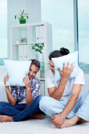 Photo for Image of guy and girl sitting on the floor with pillows by their faces - Royalty Free Image