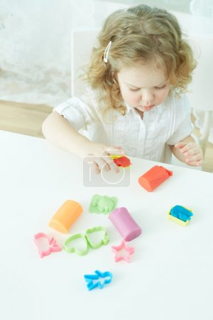 Photo for Vertical image of a little blonde playing with modeling clay - Royalty Free Image