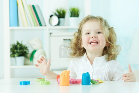 Photo for Excited child enjoying her favorite hobby playing with modeling clay - Royalty Free Image
