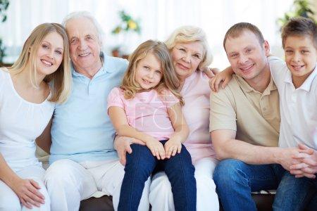 Foto de Retrato de mayores y jóvenes parejas con sus hijos mirando a cámara en casa - Imagen libre de derechos