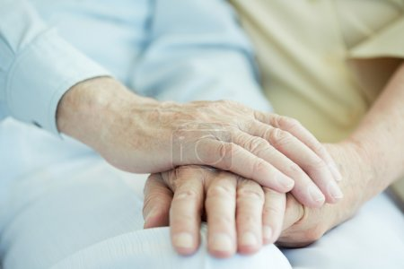 Photo for Close-up of senior male hands in hand of his wife - Royalty Free Image