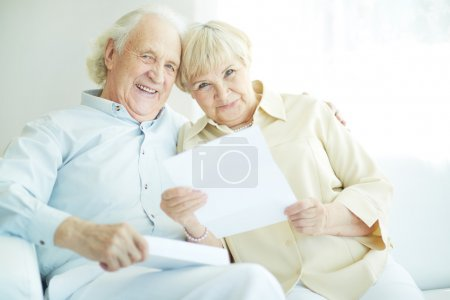 Photo for Portrait of a candid senior couple with paper looking at camera - Royalty Free Image