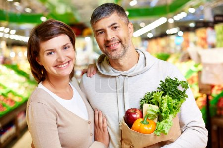 Photo for Image of happy couple with paperbag full of products looking at camera in supermarket - Royalty Free Image
