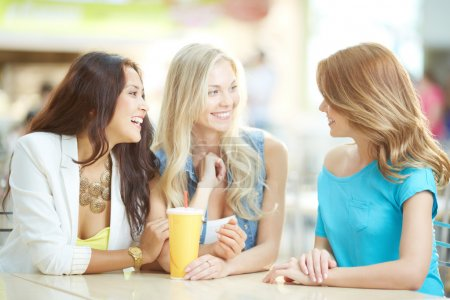 Photo for Portrait of three happy girls chatting while having drink after shopping - Royalty Free Image
