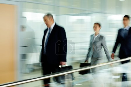 Photo for Tired businessman going along corridor with two employees behind - Royalty Free Image