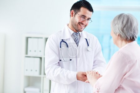 Photo for Confident doctor looking at his senior patient while speaking to her - Royalty Free Image