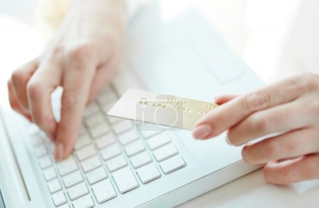 Photo pour Main féminine avec carte de crédit lors de shopping sur internet - image libre de droit