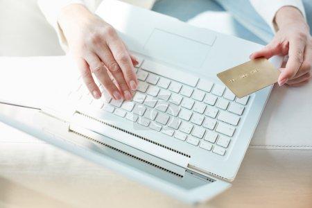 Photo pour Mains féminines avec carte de crédit pendant les achats sur Internet - image libre de droit