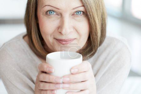 Photo for Portrait of mature woman with cup looking at camera - Royalty Free Image