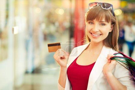 Photo pour Jolie dame montrant la carte de crédit dans le centre commercial - image libre de droit