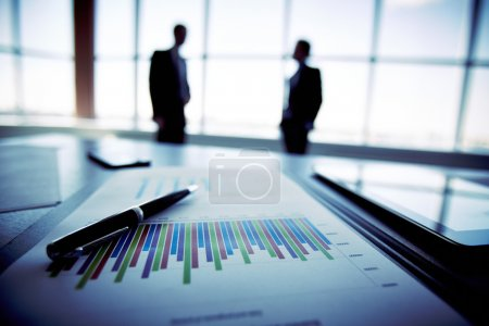 Photo for Close-up of a financial report with the silhouettes of business people in the background - Royalty Free Image