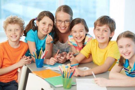 Photo pour Portrait d'écoliers joyeux et professeur à succès regardant la caméra - image libre de droit
