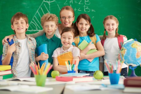 Photo for Portrait of cute schoolchildren and their teacher on background of blackboard - Royalty Free Image
