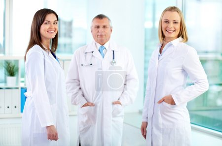 Photo for Portrait of happy nurses looking at camera with mature doctor behind - Royalty Free Image