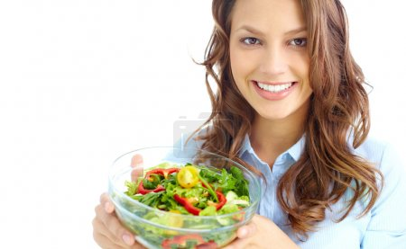 Photo for Close-up of pretty girl holding fresh vegetable salad in glass bowl - Royalty Free Image