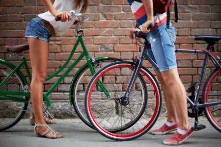 Photo for Close-up of guy and girl legs with bicycles against brick wall - Royalty Free Image
