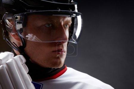 Photo pour Visage du sportif en casque de protection sur fond noir - image libre de droit