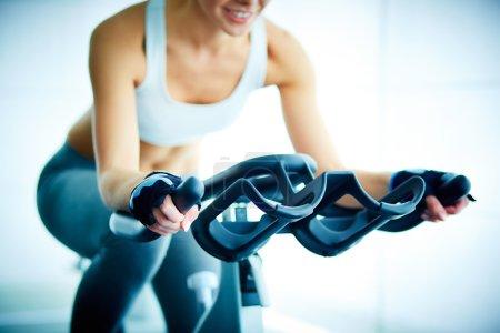 Photo pour Gros plan sur l'entraînement des jeunes femmes sur simulateur en salle de gym - image libre de droit