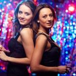 Two sensual women dressed in black posing against ...