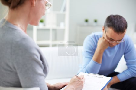 Photo pour Femelle psychologue consultant homme pensif au cours de la session de thérapie psychologique - image libre de droit