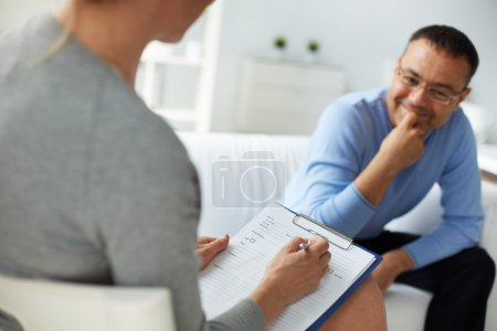 Photo for Female psychologist consulting mature man during psychological therapy session - Royalty Free Image