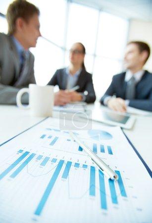 Photo pour Vue verticale d'une équipe d'affaires en réunion, mise au premier plan du rapport financier - image libre de droit