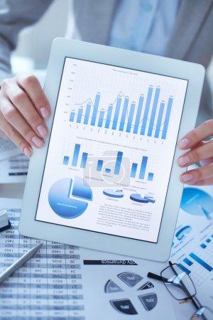 Photo pour Image verticale en gros plan d'une femme d'affaires tenant une tablette numérique avec des données financières à l'écran - image libre de droit