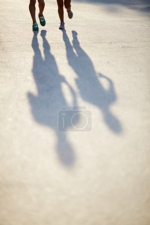 Photo for Photo of shadows of dates legs running outdoors - Royalty Free Image