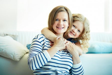 Photo for Portrait of happy girl and her mother looking at camera at home - Royalty Free Image