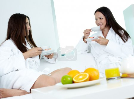 Photo for Attractive girls in bathrobes relaxing in spa and drinking tea - Royalty Free Image