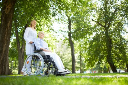 Photo for Pretty nurse walking with senior patient in a wheelchair in park - Royalty Free Image