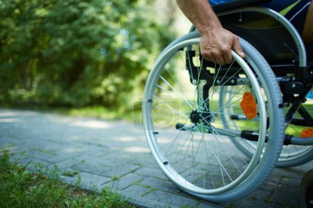 Photo for Close-up of male hand on wheel of wheelchair during walk in park - Royalty Free Image