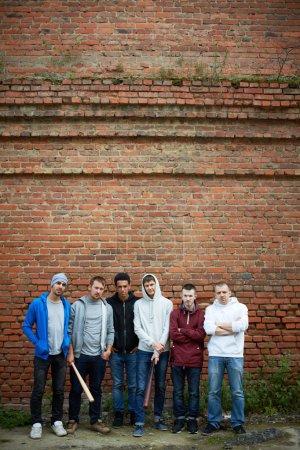 Photo pour Portrait de plusieurs rues hooligans ou rappeurs debout contre le mur de briques - image libre de droit