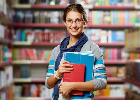 Photo pour Portrait d'étudiant intelligent avec des livres dans la bibliothèque du collège - image libre de droit