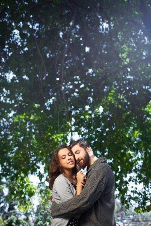 Photo pour Image d'affectueux jeune homme embrasser tendrement sa date à l'extérieur - image libre de droit