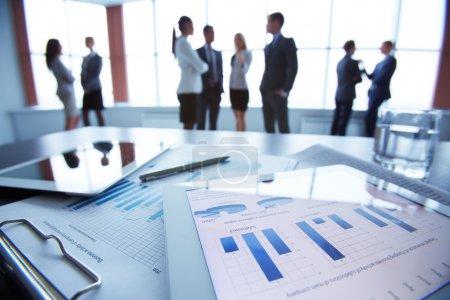 Photo pour Gros plan du document d'affaires dans le pavé tactile couché sur le bureau, les employés de bureau interagissent en arrière-plan - image libre de droit