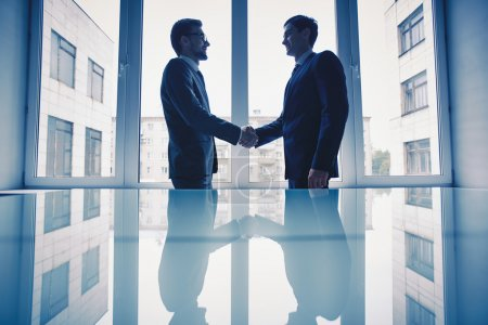 Photo for Photo of successful businessmen handshaking after striking deal - Royalty Free Image