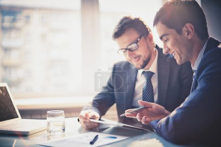 Photo for Image of two young businessmen using touchpad at meeting - Royalty Free Image
